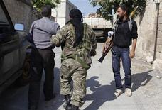 Un vídeo que parece mostrar a rebeldes sirios matando a unos soldados que se habían rendido constituye probablemente un crimen de guerra que debería ser perseguido, dijo el viernes la oficina de derechos humanos de la ONU. En la imagen del 28 de octubre, unos combatientes del Ejército Libre de Siria se llevan a un hombre detenido (izq.) sospechoso de ser miembro de las fuerzas gubernamentales, en la localidad de Haram, en el comisionado de Idlib. REUTERS/Asmaa Waguih