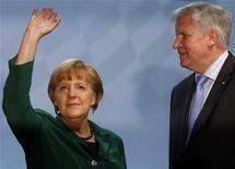 La canciller alemana, Angela Merkel, está bajo presión para resolver este fin de semana una disputa sobre los impuestos y las ayudas sociales entre sus socios de la coalición en el poder, a fin de exhibir un frente unido de cara a las elecciones de 2013. Imagen de Merkel con el primer ministro de Baviera, Horst Seehofer, antes de dar un discurso en la reunión de la Unión Social Cristiana de Baviera (CSU) - partido hermano del cristianodemócrata (CDU) de la canciller - celebrada el 19 de octubre en Múnich. REUTERS/Michael Dalder