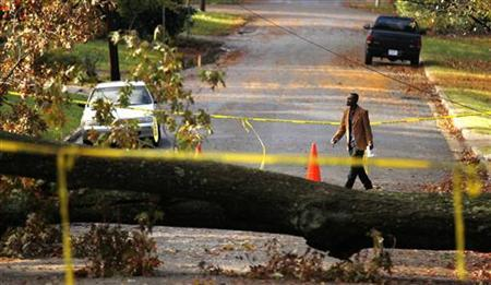 A man walks past a tree, which has fallen over during Hurricane Sandy, in Falls Church, Virginia October 31, 2012. REUTERS/Kevin Lamarque