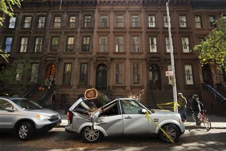 The trunk of a tree remains on top of a luxury SUV following Hurricane Sandy in the Brooklyn borough of New York November 2, 2012. REUTERS/Lucas Jackson