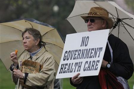 People hold signs at a Tea Party Patriots rally calling for the repeal of the 2010 healthcare law championed by President Barack Obama, on Capitol Hill in Washington, March 24, 2012. REUTERS/Jonathan Ernst