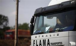 <p>Un camionero apoya sus pies sobre el salpicadero de su camión mientras espera poder descargar granos en el terminal America Latina Logistica en Alto de Araguaia, Brasil, sep 24 2012. La vista desde la cabina del camión de Marcondes Mendonça ayuda a entender el éxito de los agronegocios en Brasil: modernas cosechadoras peinan día y noche campos de granos que se extienden hasta donde alcanzan los ojos. REUTERS/Nacho Doce</p>
