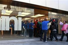 Apple employees share high-fives with customers who has been waiting in line to purchase the new iPad minis at Apple Store Ginza in Tokyo November 2, 2012. REUTERS/Yuriko Nakao