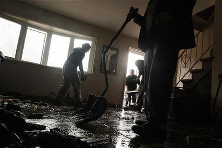 A family works with snow shovels to clean the mud and flood debris out of their home in the New Dorp Beach neighborhood of the Staten Island borough of New York, November 1, 2012. REUTERS/Lucas Jackson