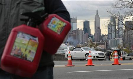 A man waits in line to buy gas at a station, as the Empire State Building and the skyline of New York is seen in the background, at Union City, New Jersey November 2, 2012. REUTERS/Eduardo Munoz