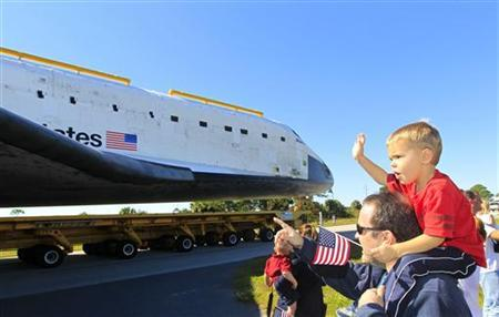 Kyle Wallace, 3, sits atop his father David's shoulders while waving as the space shuttle Atlantis is moved to its new home in the Visitors Center at the Kennedy Space Center in Cape Canaveral, Florida November 2, 2012. REUTERS/Joe Skipper