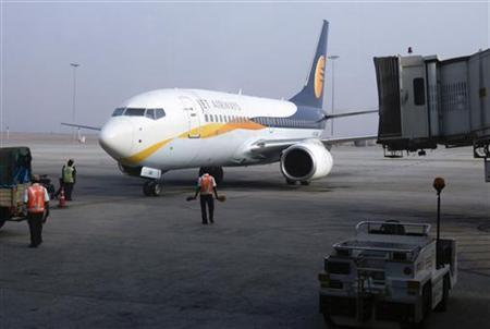 Ground staff guide a Jet Airways aircraft towards a gate on the tarmac at Bengaluru International Airport in Bangalore March 5, 2012. REUTERS/Vivek Prakash/Files