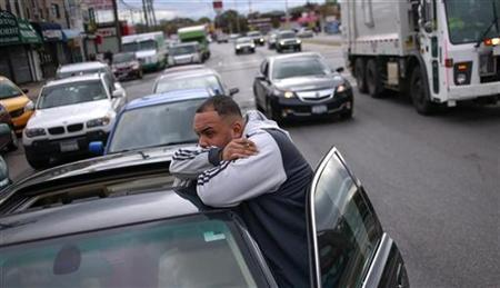 A man looks towards a gas station while waiting for hours with hundreds of others to fuel up their vehicles in the New York City borough of Queens on November 1, 2012. REUTERS/Adrees Latif