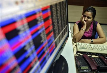An investor watches the share index in Chandigarh June 18, 2012. REUTERS/Ajay Verma/Files