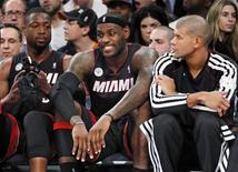 Miami Heat forward LeBron James reacts as he joins guard Dwyane Wade (L) and forward Shane Battier (R) on the bench during their loss to the New York Knicks in the fourth quarter of their NBA basketball game at Madison Square Garden in New York November 2, 2012. REUTERS/Ray Stubblebine