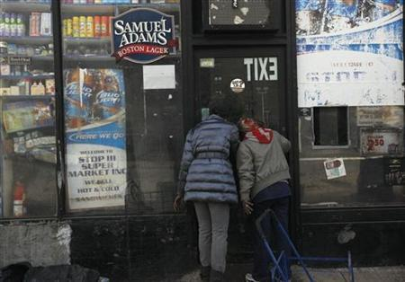 Two women look into the window of a flooded deli while searching for food in Coney Island, New York, November 2, 2012. Four days after Sandy smashed into the Northeast, rescuers were still discovering the extent of the death and devastation, and anger mounted over gasoline shortages, power outages and waits for relief supplies. REUTERS/Brendan McDermid (UNITED STATESDISASTER ENVIRONMENT - Tags: DISASTER ENVIRONMENT ENERGY FOOD)