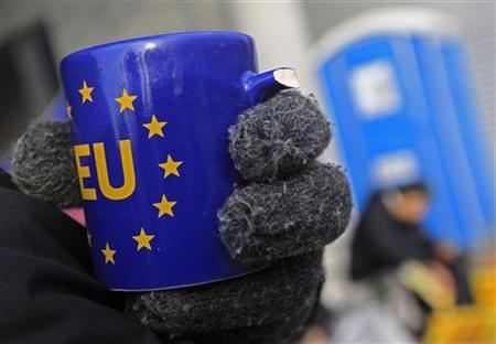 A person on a hunger strike drinks hot tea out of a broken European Union mug in front of the office building of Hungary's public broadcaster in Budapest December 20, 2011. Camped outside Hungary's public broadcaster, a small group of television editors is on hunger strike to protest what they say is widespread news manipulation by the government. REUTERS/Laszlo Balogh (HUNGARY - Tags: POLITICS CIVIL UNREST MEDIA)
