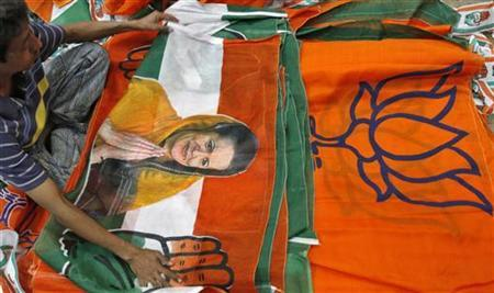 A worker looks at a Congress party flag carrying a picture of its party chief Sonia Gandhi next to flags of opposition Bharatiya Janata Party (BJP) inside an election campaigning material workshop in Ahmedabad October 10, 2012. REUTERS/Amit Dave