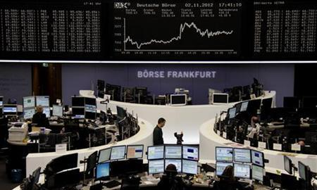 Traders are pictured at their desks in front of the DAX board at the Frankfurt stock exchange November 2, 2012. REUTERS/Remote/Staff (GERMANY - Tags: BUSINESS)
