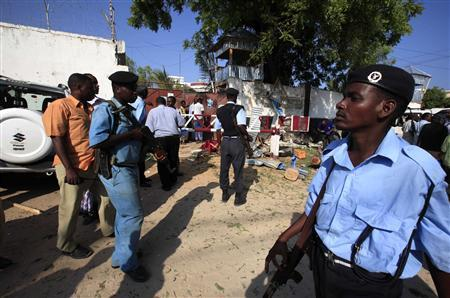 Somali policemen mill around the scene of a suicide attack in capital Mogadishu November 3, 2012. Two suicide bombers attacked a restaurant in the Somali capital on Saturday, killing a security guard who stopped them entering the building, locals said. REUTERS/Omar Faruk