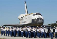 El último transbordador espacial de la NASA abandonó el viernes un hangar de Florida y fue trasladado al cercano Complejo para Visitantes del Centro Espacial Kennedy para comenzar su nueva vida como pieza de museo. En la imagen, la Orquesta del Instituto Titusville marcha junto al Atlantis en su traslado. REUTERS/Joe Skipper