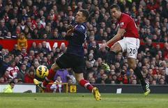 """El delantero del Manchester United Robin van Persie estaba bajo los focos el sábado por el reencuentro con su ex equipo, el Arsenal, en un partido en el que los """"diablos rojos"""" se impusieron al equipo londinense por 2-1. En la imagen, Van Persie (derecha), del Manchester United, dispara ante el defensa del Arsenal Thomas Vermaelen. REUTERS/Darren Staples"""