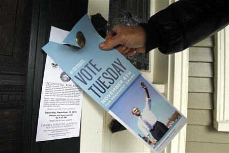 David Ewing hangs a piece of campaign literature on a door knob as he canvasses for U.S. President Barack Obama in Portsmouth, New Hampshire November 3, 2012. REUTERS/Jessica Rinaldi