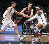 Toronto Raptors center Andrea Bargnani (7) tries to pass between Brooklyn Nets center Brook Lopez (L) and forward Gerald Wallace (R) in the first quarter of their NBA basketball game in New York, November 3, 2012. REUTERS/Ray Stubblebine