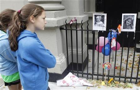 A young girl looks at a makeshift memorial left outside the Krim family apartment in New York, October 28, 2012. REUTERS/Carlo Allegri