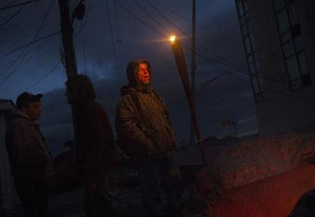 Louis Decarolis stands next to a fire outside his home on Beach 91st street in the Rockaways section of the Queens borough of New York November 3, 2012. REUTERS/Shannon Stapleton