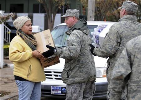 Members of the New York Air National Guards 174th Attack Wing bring food and water to a local woman on Staten Island in New York in this November 2, 2012 handout photo obtained by Reuters November 3. REUTERS/New York Air National Guard/Jeremy M. Call/Handout