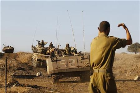 An Israeli soldier signals as an armoured personnel carrier (front) advances during a drill near the northern city of Katzrin in the Golan Heights September 19, 2012. REUTERS/Baz Ratner/Files