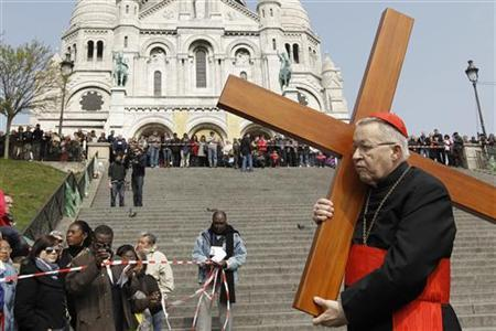 French Archbishop of Paris Cardinal Andre Vingt-trois carries a cross in the gardens of the Montmartre's Sacre Coeur Basilica during the annual Good Friday ''Stations of the Cross'' procession in Paris April 6, 2012. REUTERS/Gonzalo Fuentes/Files