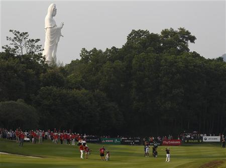 Louis Oosthuizen (R) of South Africa hits on the 18th fairway in front of a Buddhist Guanyin statue during the third day of the WGC-HSBC Champions Tournament at Mission Hills in the southern Chinese city of Dongguan November 3, 2012. REUTERS/Bobby Yip