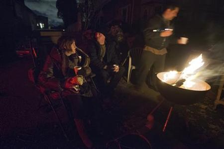 Victims of hurricane Sandy sit near a fire to stay warm outside their destroyed homes in the Staten Island borough of New York November 3, 2012. REUTERS/Adrees Latif