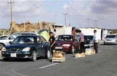 People from Tarhunah distribute food and aid to families returning to Bani Walid, at the first checkpoint on the road to the town, November 3, 2012. REUTERS/Ismail Zitouny