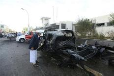 A man looks into a police car, which exploded after an explosive device was detonated in the parked vehicle, in front of a police station in in Benghazi November 4, 2012. REUTERS/Esam Al-Fetori