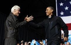 La carrera por la presidencia de Estados Unidos, que ha dependido durante meses de un puñado de estados, convergió el sábado en una ciudad en Iowa en la que tanto el presidente, Barack Obama, como el aspirante republicano, Mitt Romney, hicieron un llamamiento de última hora para animar a los votantes de cara a los comicios del martes. En la imagen del 3 de noviembre, Obama saluda al ex presidente Bill Clinton en otro mitin celebrado en Bristow, Virginia. REUTERS/Jason Reed