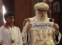 Egyptian caretaker of the Coptic Church, interim Pope Bakhomious (R) holds a piece of paper with the name of Bishop Tawadros written on it, after it was picked by Bishoy Gerges in Cairo November 4, 2012. Egypt's Coptic Orthodox church chose a new pope, Bishop Tawadros, in a sumptuous service on Sunday that Christians hope will lead them through an Islamist-dominated landscape and protect what is the Middle East's biggest Christian community. REUTERS/Mohamed Abd El Ghany