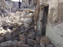 Homem caminha entre escombros depois que um jato da Força Aérea da Síria atirou mísseis em Binsh, Síria. Uma explosão ocorreu próxima das instalações de um sindicato estatal atrás de um hotel na capital da Síria, Damasco, neste domingo, deixando muitos feridos, disse a TV estatal do país. 03/11/2012 REUTERS/Muhammad Najdet Qadour/Shaam News Network/Handout