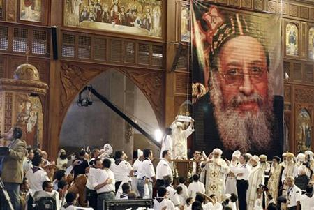 Egyptian caretaker of the Coptic Church, interim Pope Bakhomious (C) holds a piece of paper with the name of Bishop Tawadros written on it, after it was picked by Bishoy Gerges in Cairo November 4, 2012. REUTERS/Mohamed Abd El Ghany