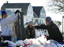 Moradores escolhem roupas doadas deixadas na rua para as vítimas da tempestade Sandy no bairro do Queens em Nova York, EUA. Vítimas da tempestade Sandy na Costa Leste dos Estados Unidos lutavam para se proteger do frio neste domingo em meio à escassez de combustível e falta de energia. 04/11/2012 REUTERS/Lucas Jackson