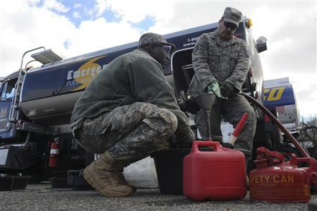 Army Sgt. Adama Ilbouda (L) with the New York Army National Guard, and Tech. Sgt. David Tayler, distribute fuel at the Staten Island Armory following Hurricane Sandy in this November 3, 2012 handout photo courtesy of the U.S. Army. The fuel, available at no charge to those who needed it, was provided by the Federal Emergency Management Agency and distributed at various armories throughout the New York and northern New Jersey areas. Picture taken November 3, 2012. REUTERS/U.S. Army/Sgt. 1st Class Jon Soucy/Handout