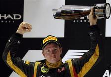 Lotus F1 Formula One driver Kimi Raikkonen of Finland lifts his trophy after winning the Abu Dhabi F1 Grand Prix at the Yas Marina circuit on Yas Island November 4, 2012. REUTERS/Darren Whiteside