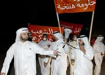 "Kuwaiti protesters hold up signs reading, ""New government, elected government"" during an impromptu protest that was dispersed by tear gas in Sabah al Salem districts November 4, 2012. REUTERS/Stephanie Mcgehee"