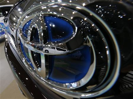 Toyota's cars are reflected on its logo on Prius PHV at its showroom in Tokyo October 23, 2012. REUTERS/Kim Kyung-Hoon