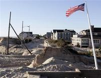 A U.S. flag flies from a flagpole tilting in the sand south of East Avenue in Bay Head, New Jersey, November 4, 2012 in the aftermath of Hurricane Sandy. REUTERS/Tom Mihalek