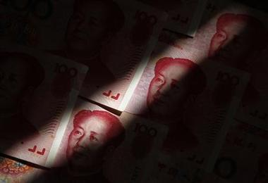 File photo of beam of light falling on Chinese 100 yuan banknotes in this...