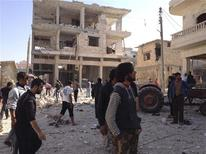 Residents walk on rubble near buildings which are damaged after a Syrian Air Force fighter jet loyal to Syria's President Bashar al-Assad fired missiles at Binsh, near the northern province of Idlib November 3, 2012. Picture taken November 3, 2012. REUTERS/Muhammad Najdet Qadour/Shaam News Network/Handout