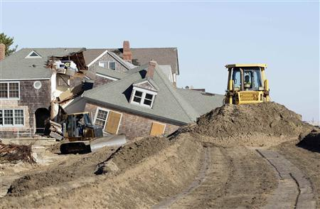 Bulldozers push sand across the top of a rock sea wall with the remains of a beach front home that was torn in half by the force of the water in Bay Head, New Jersey, November 4, 2012 in the aftermath of Hurricane Sandy. REUTERS-Tom Mihalek