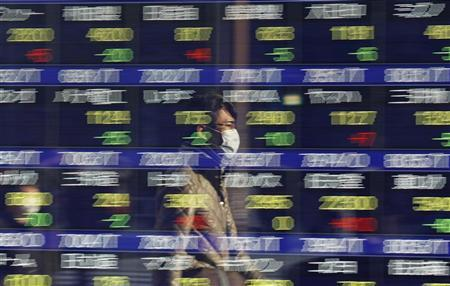 A man is reflected on a stock market board at a business district in Tokyo December 30, 2009. REUTERS/Toru Hanai/Files