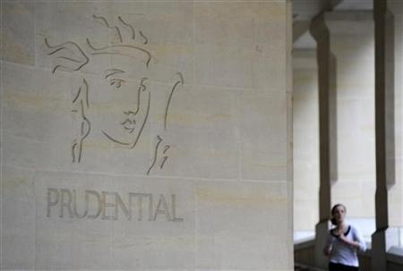 A woman passes the Prudential offices in central London May 13 2010. REUTERS/Paul Hackett