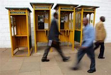 People walk past telephone booths in the streets of Kenya's capital Nairobi, September 12, 2006. REUTERS/Antony Njuguna