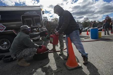 National Guardsmen put gasoline into canisters at a temporary National Guard fueling center in the Staten Island Borough of New York, November 3, 2012, in the aftermath of Hurricane Sandy. REUTERS/Keith Bedford