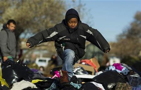 A boy runs through a pile of donated clothing that had been left on the street for victims of superstorm Sandy in the Rockaways neighborhood of the Queens borough of New York, November 4, 2012. REUTERS/Lucas Jackson
